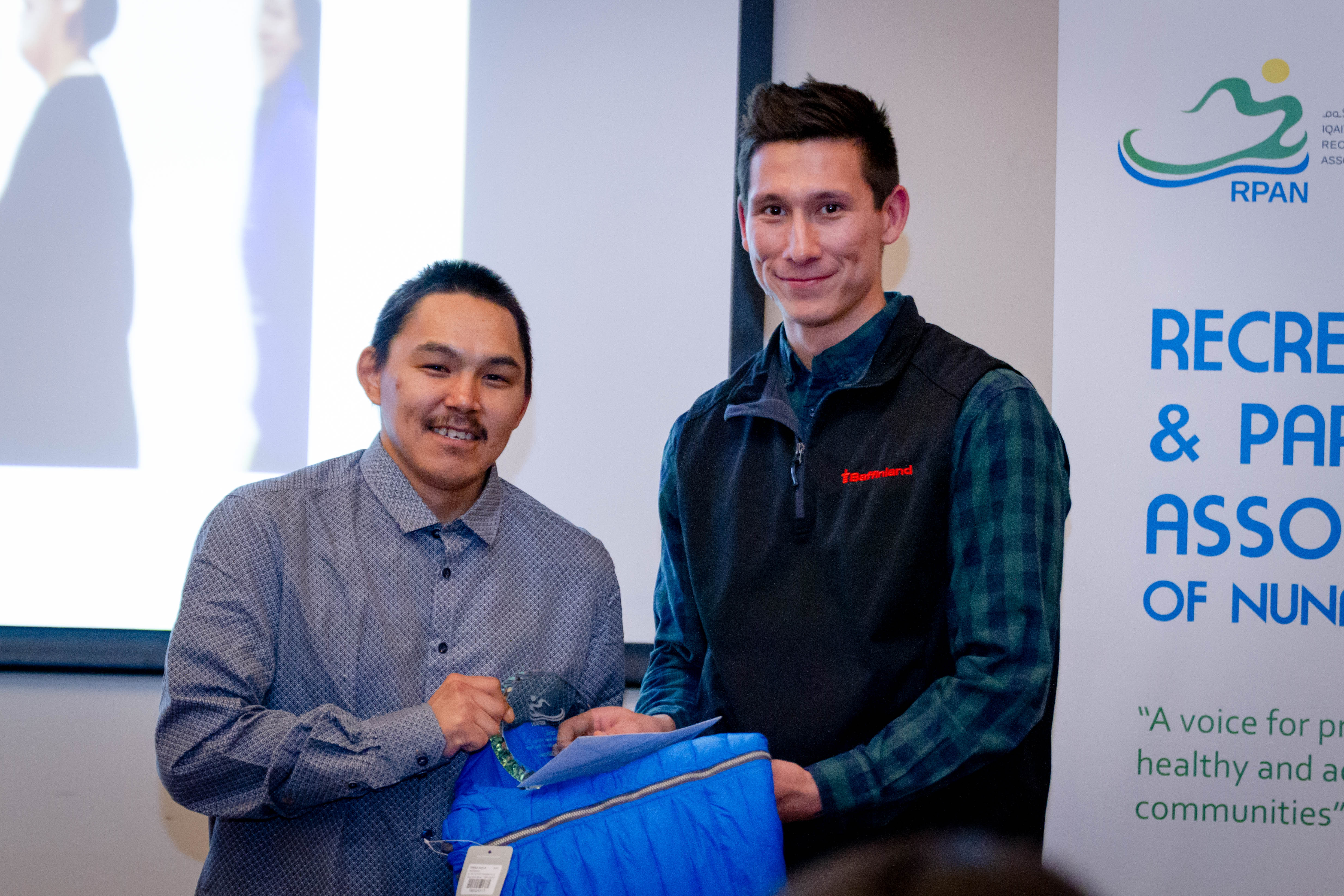 Devin Aviugana, assistant manager of Northern Affairs, presents Terry Killiktee of Clyde River with the Baffinland Iron Mines Recreation Leader of the Year award